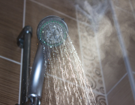 Shower head with boiling water and steam in the bathroom